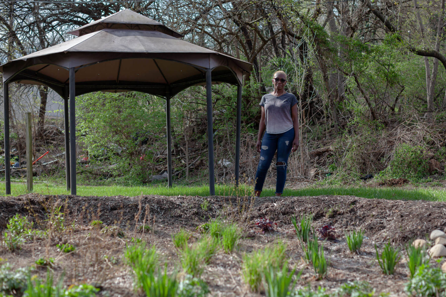 Betty Foster-Pinkley stands in front of a rain garden that UpstreamPgh, an environmental nonprofit, installed in her backyard. (Photo by Quinn Glabicki/PublicSource)